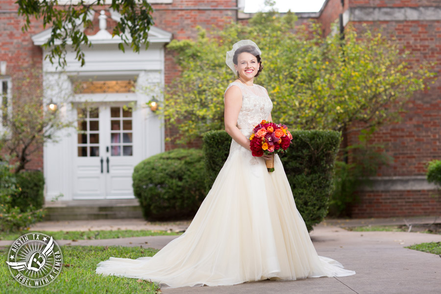 Wedding picture of happy bride with vintage bridal gown and accessories and red and orange bouquet from Bouquets of Austin outside at the Texas Federation of Women's Clubs Headquarters in Austin, Texas