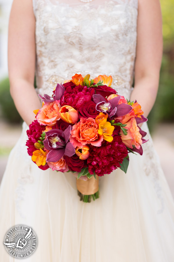 Wedding picture of red and orange bouquet from Bouquets of Austin outside at the Texas Federation of Women's Clubs Headquarters in Austin, Texas