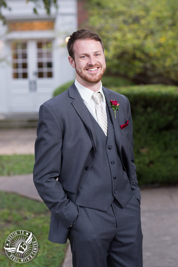 Wedding picture of happy groom with red rose boutonniere from Bouquets of Austin outside at the Texas Federation of Women's Clubs Headquarters in Austin, Texas