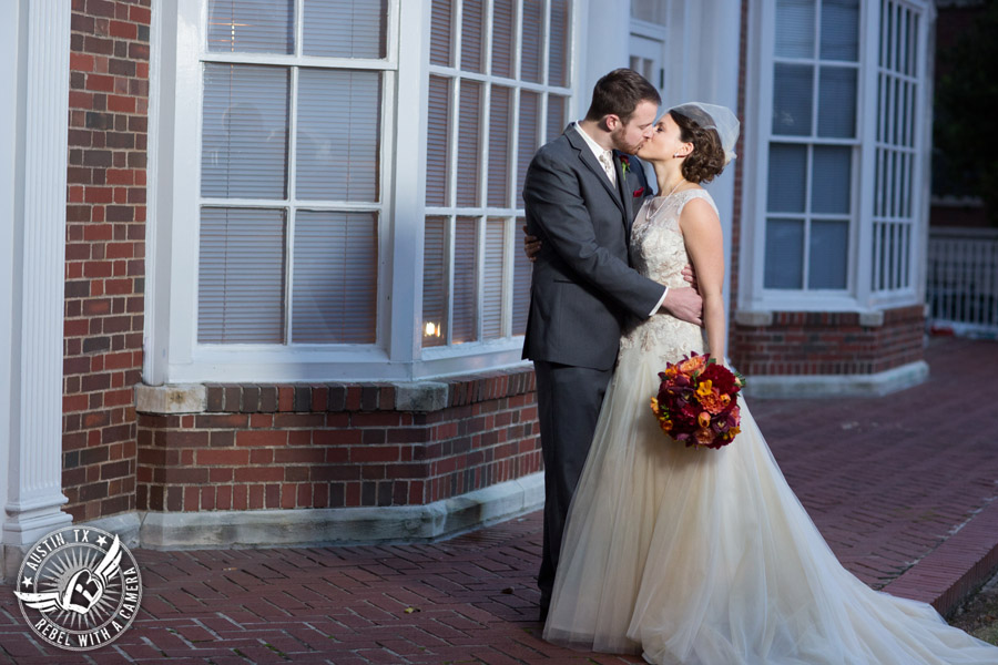 Wedding picture of happy bride and groom kissing with bouquet by Bouquets of Austin outside at the Texas Federation of Women's Clubs Headquarters in Austin, Texas