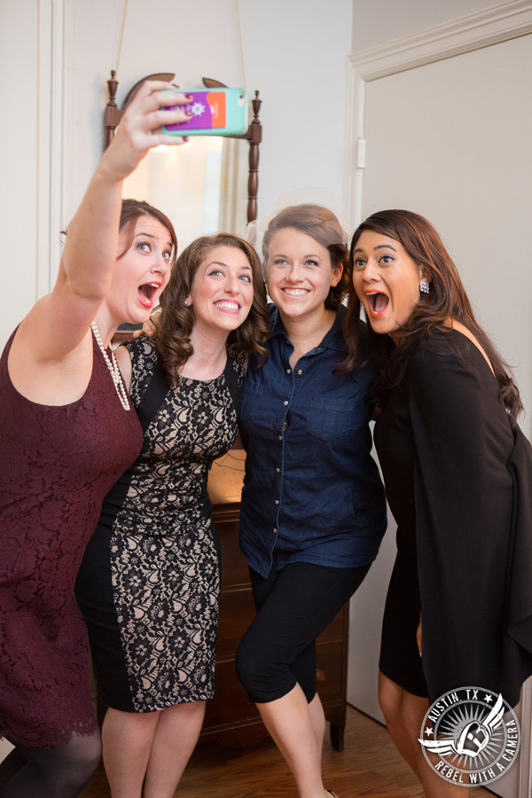 Wedding picture of the bride taking a selfie with friends in the bride's room at the Texas Federation of Women's Clubs Headquarters in Austin, Texas