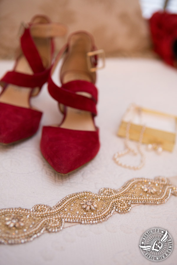 Wedding picture of the bride's red suede shoes, pearl jewelry, and golden beaded sash in the bride's room at the Texas Federation of Women's Clubs Headquarters in Austin, Texas