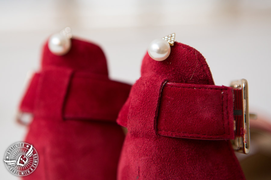 Wedding picture of the bride's pearl earrings and red suede shoes in the bride's room at the Texas Federation of Women's Clubs Headquarters in Austin, Texas