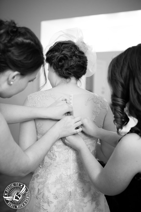Wedding picture of buttoning the bride's dress on in the bride's room at the Texas Federation of Women's Clubs Headquarters in Austin, Texas