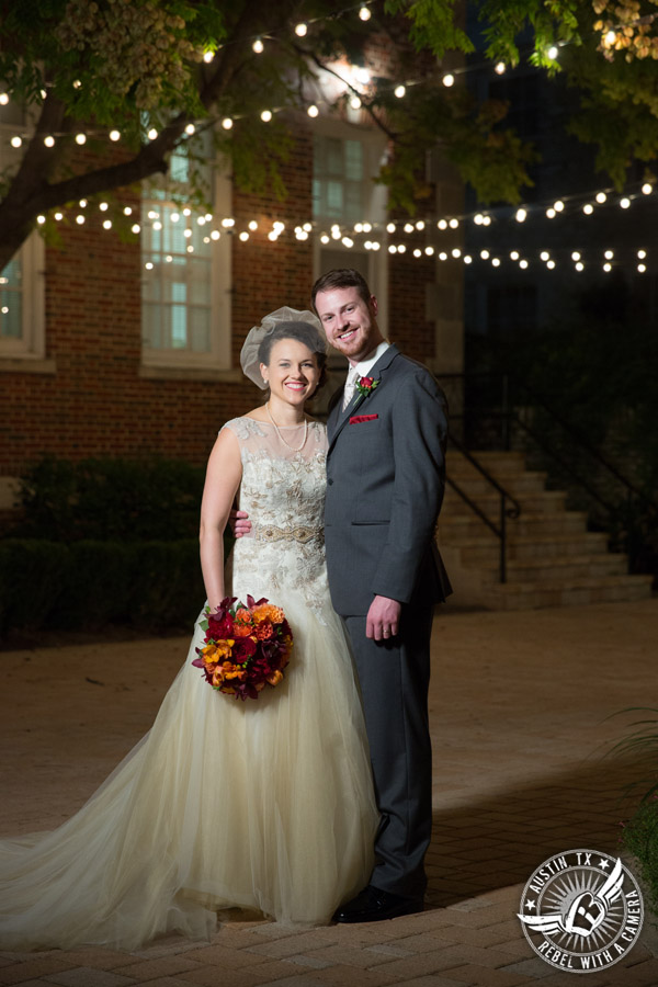Wedding picture of happy bride and groom with bouquet by Bouquets of Austin and twinkly lights outside in the courtyard at the Texas Federation of Women's Clubs Headquarters in Austin, Texas.