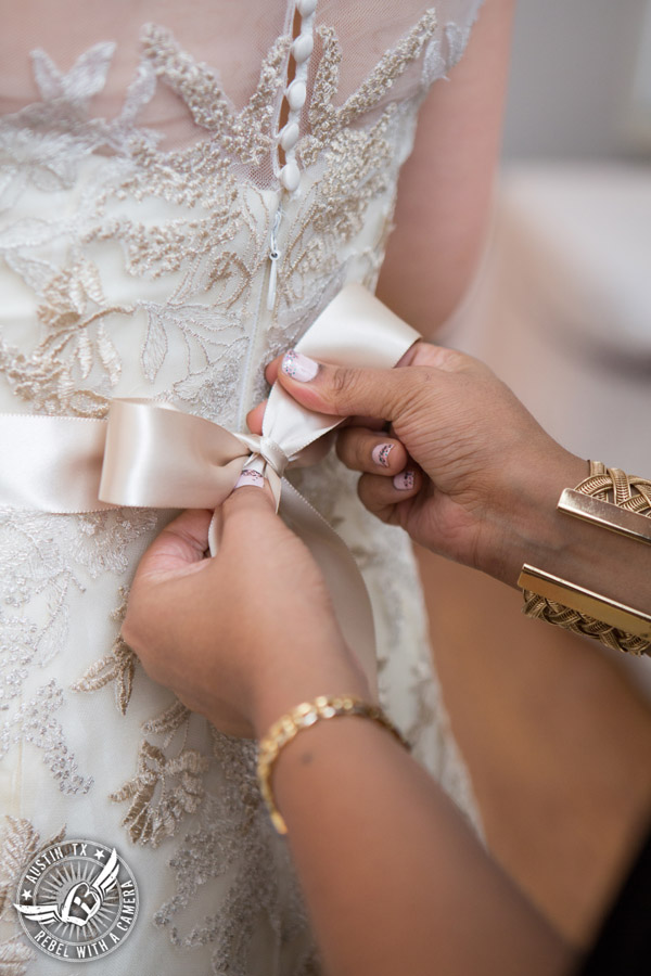 Wedding picture of tying the bride's ribbon sash in the bride's room at the Texas Federation of Women's Clubs Headquarters in Austin, Texas