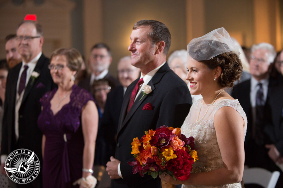 Wedding picture of the bride and her dad walking down the aisle in at the wedding ceremony in the ballroom at the Texas Federation of Women's Clubs Headquarters in Austin, Texas