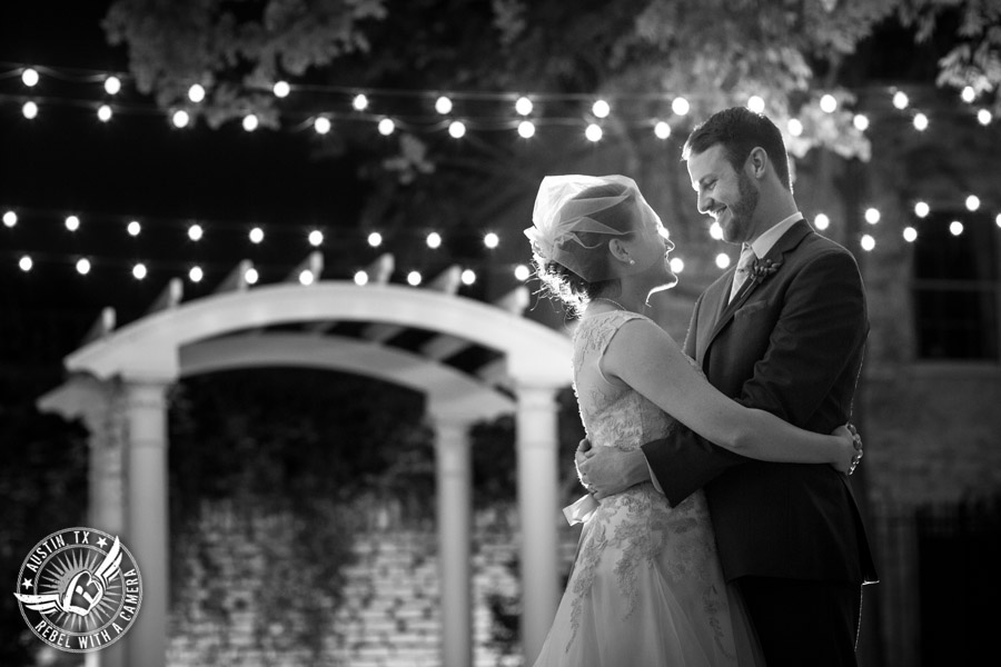 Wedding photo of happy bride and groom looking at each other under the twinkly lights outside at the Texas Federation of Women's Clubs Headquarters in Austin, Texas