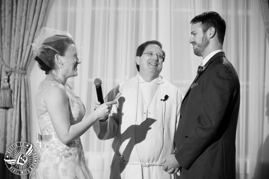 Wedding picture of the bride and groom taking their vows at the wedding ceremony in the ballroom at the Texas Federation of Women's Clubs Headquarters in Austin, Texas
