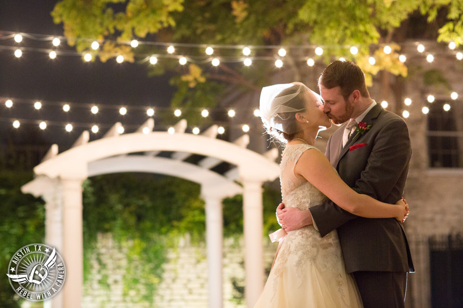 Wedding picture of happy bride and groom kissing under the twinkly lights outside at the Texas Federation of Women's Clubs Headquarters in Austin, Texas