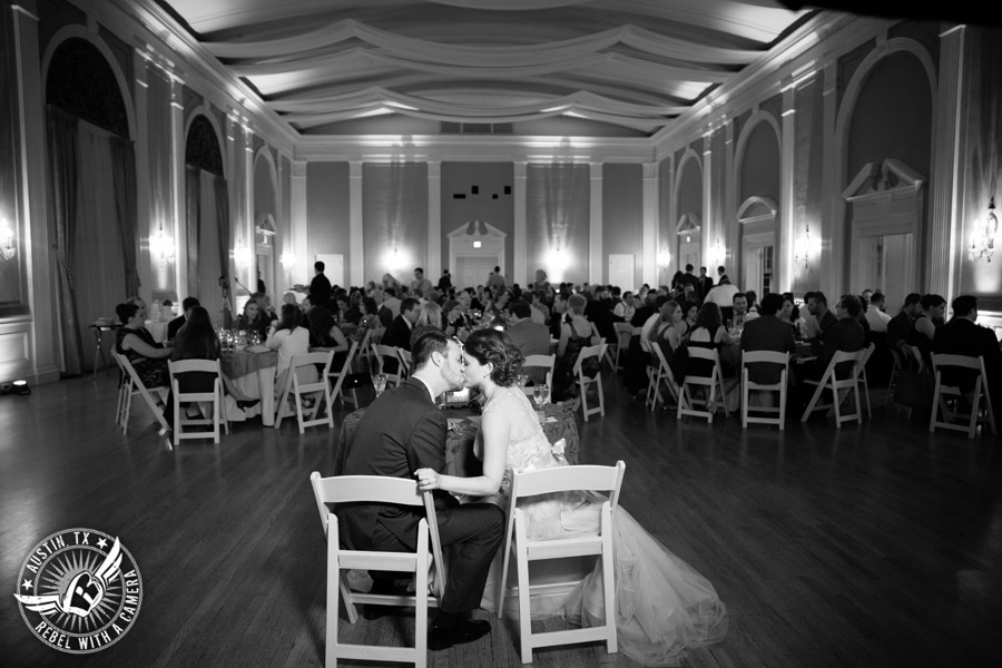 Wedding picture of the bride and groom kissing at the reception in the ballroom at the Texas Federation of Women's Clubs Headquarters in Austin, Texas