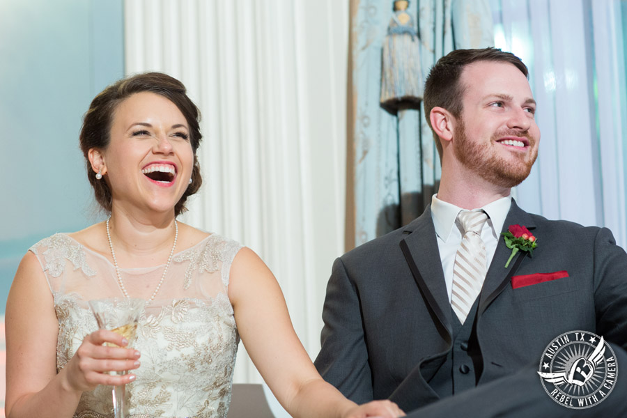 Wedding picture of the bride and groom laughing during the speeches at the reception in the ballroom at the Texas Federation of Women's Clubs Headquarters in Austin, Texas