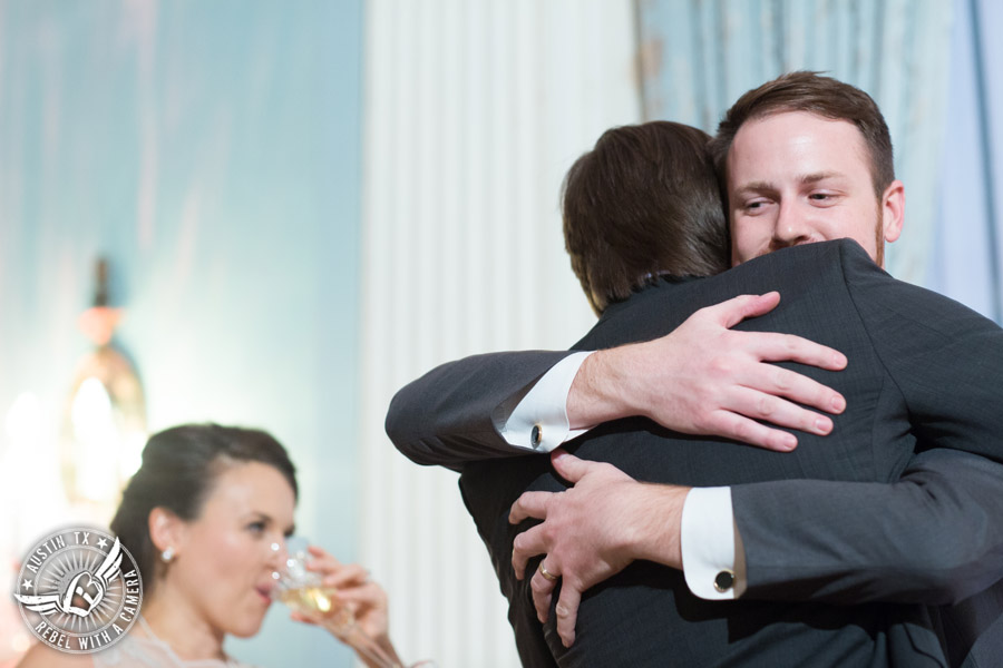 Wedding picture of the groom hugging the bride's brother during the speeches at the reception in the ballroom at the Texas Federation of Women's Clubs Headquarters in Austin, Texas