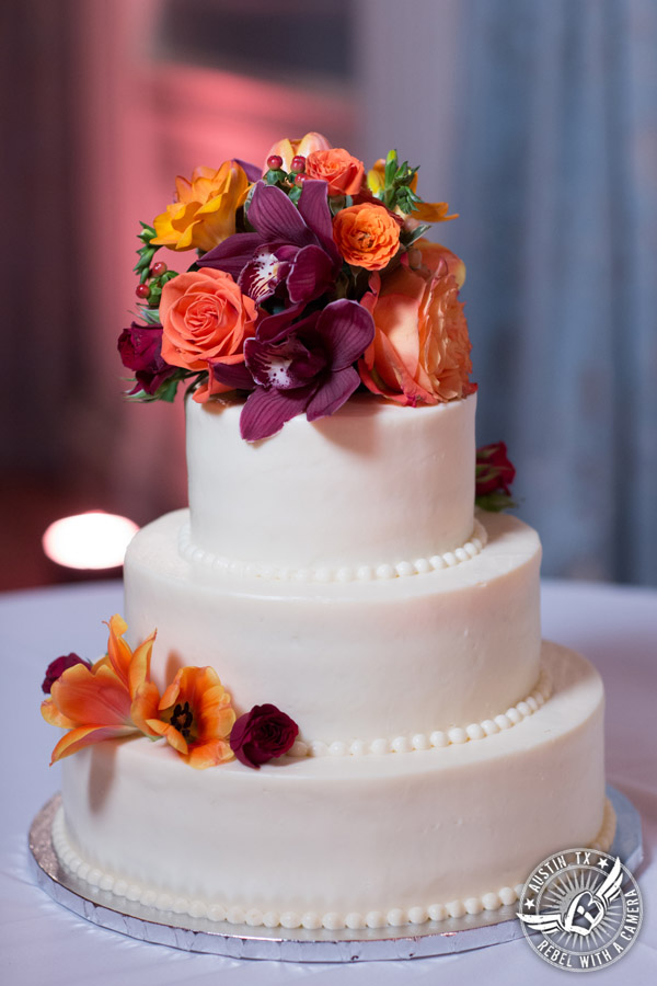 Wedding picture of white buttercream wedding cake from Central Market with autumn colored flowers from Bouquets of Austin at the reception in the ballroom at the Texas Federation of Women's Clubs Headquarters in Austin, Texas