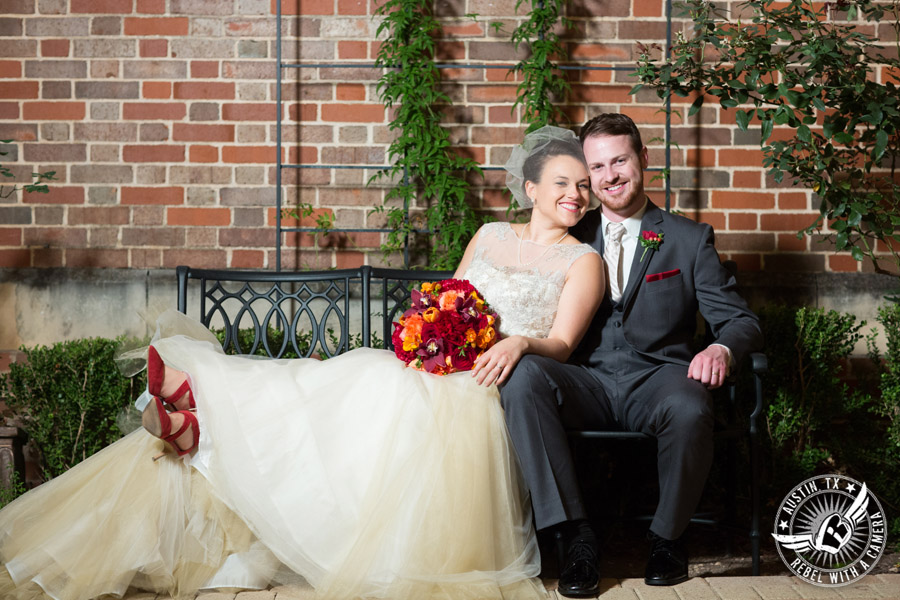 Wedding picture of happy bride and groom with red and orange bouquet from Bouquets of Austin sitting on bench in the courtyard at the Texas Federation of Women's Clubs Headquarters in Austin, Texas