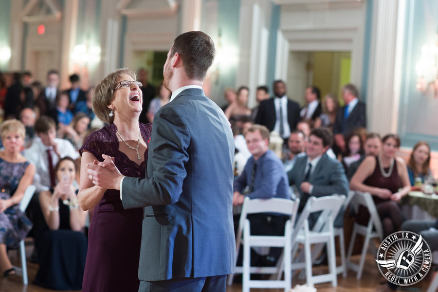 Wedding picture of groom dancing with mother with Byrne Rock DJ at the reception in the ballroom at the Texas Federation of Women's Clubs Headquarters in Austin, Texas