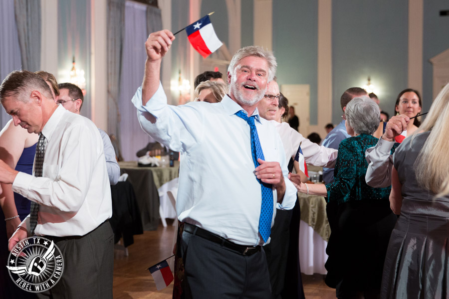Wedding picture of guest dancing and waving Texas flag with Byrne Rock DJ at the reception in the ballroom at the Texas Federation of Women's Clubs Headquarters in Austin, Texas