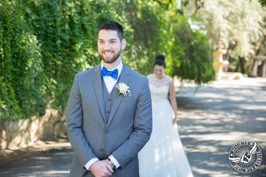 Beautiful wedding pictures on Lake Travis - first look between bride in Maggie Sottero wedding gown with groom in blue bow tie