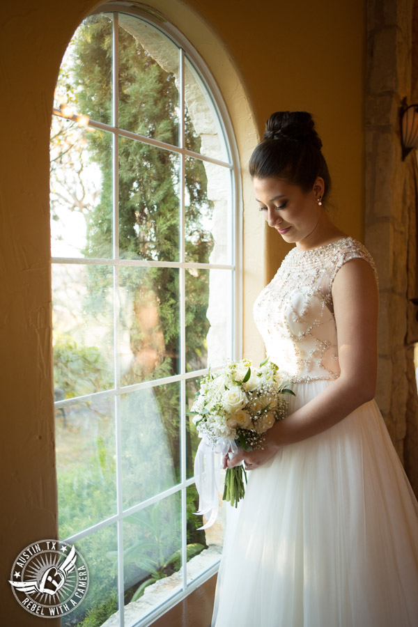 Beautiful wedding pictures on Lake Travis - bride in Maggie Sottero wedding gown by window before the wedding ceremony