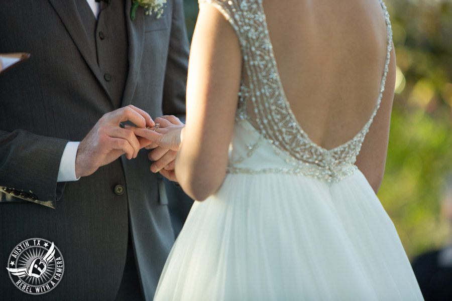 Beautiful wedding pictures on Lake Travis - bride and groom exchange rings during the wedding ceremony at the arbor