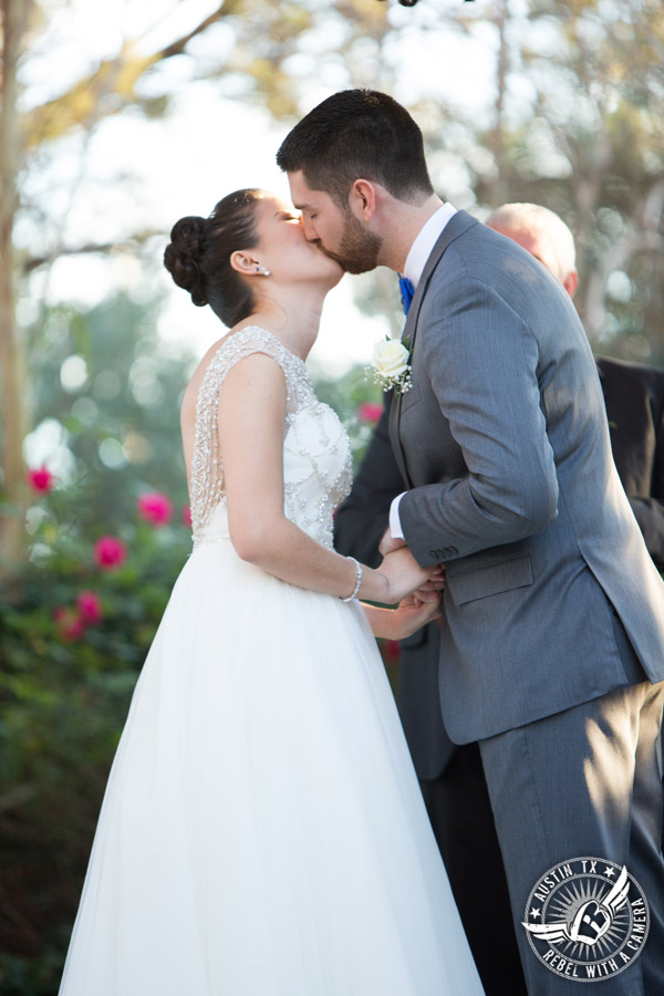 Beautiful wedding pictures on Lake Travis - bride and groom kiss at the end of the wedding ceremony at the arbor