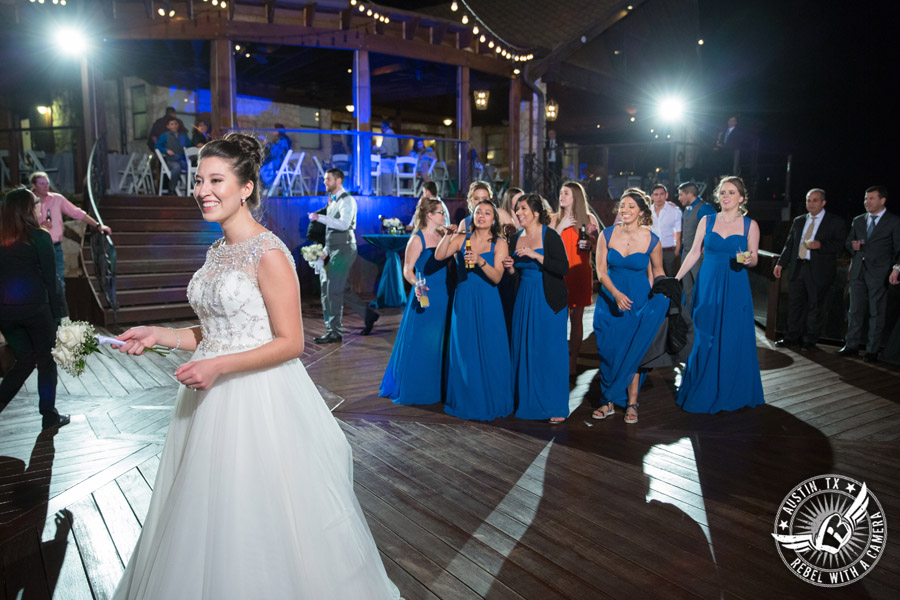 Beautiful wedding pictures on Lake Travis - bride throws bouquet during wedding reception with Greenbelt DJ