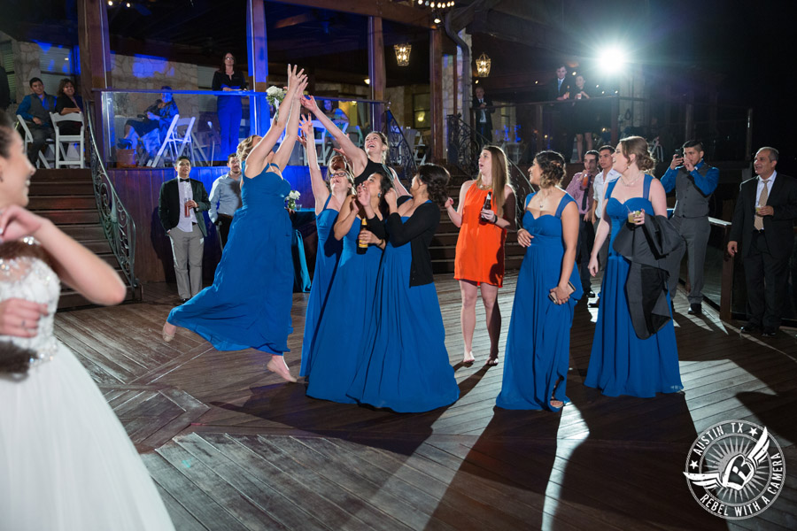 Beautiful wedding pictures on Lake Travis - bridesmaids catch bouquet during wedding reception with Greenbelt DJ