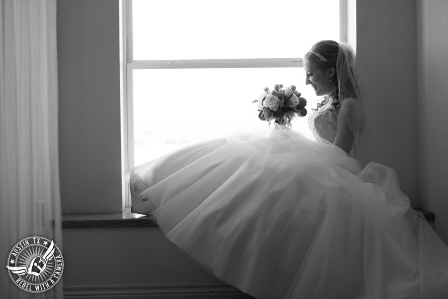 Fun Wedding Pictures at TerrAdorna in Austin, Texas - bride in window seat with bouquet in bridal suite - hair and makeup by ATX Bridal Beauty