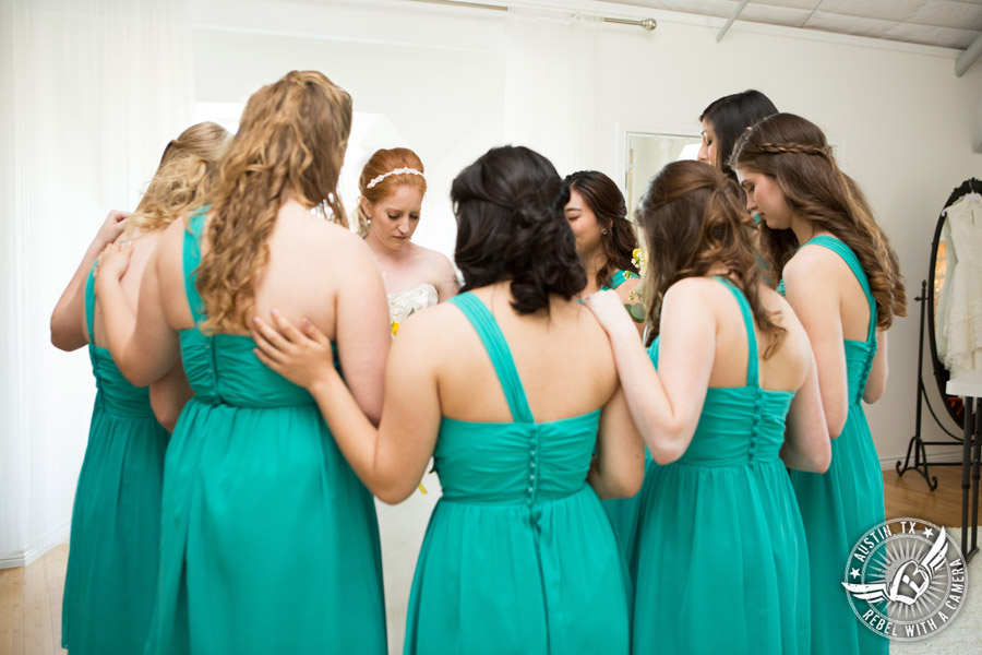 Fun Wedding Pictures at TerrAdorna in Austin, Texas - bride prays with bridesmaids in bride's room before the ceremony
