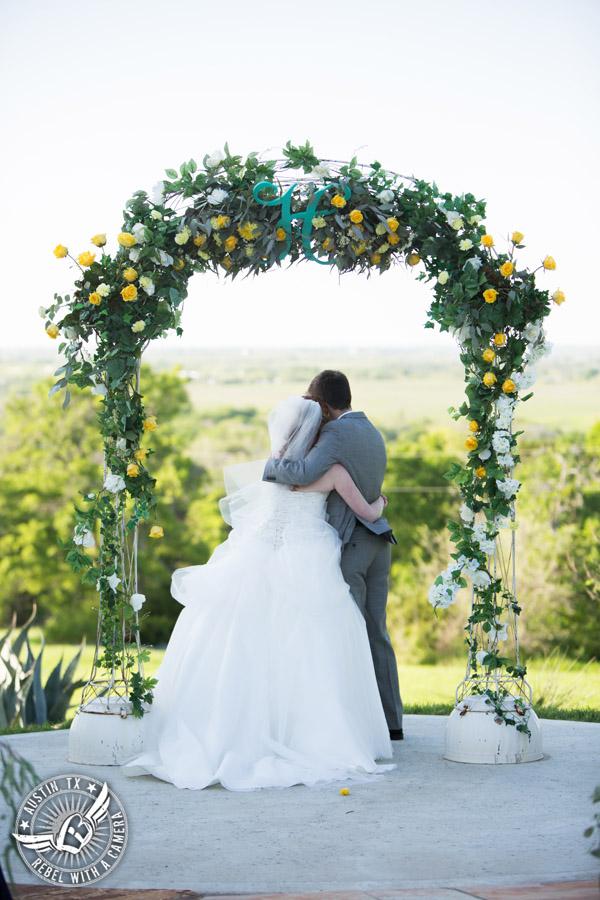 Fun Wedding Pictures at TerrAdorna in Austin, Texas - groom embraces bride during the wedding ceremony