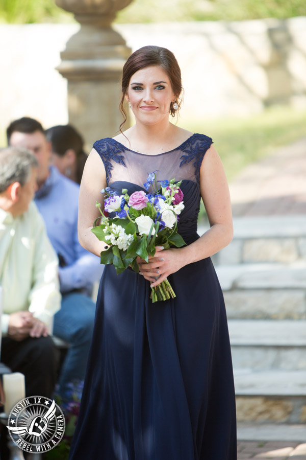 Lake Travis wedding pictures in Austin, Texas - Nature's Point - bridesmaid walks down the aisle during wedding ceremony with bouquet by Visual Lyrics