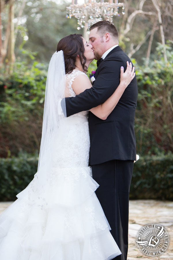 Lake Travis wedding pictures in Austin, Texas - Nature's Point - bride and groom kiss during wedding ceremony