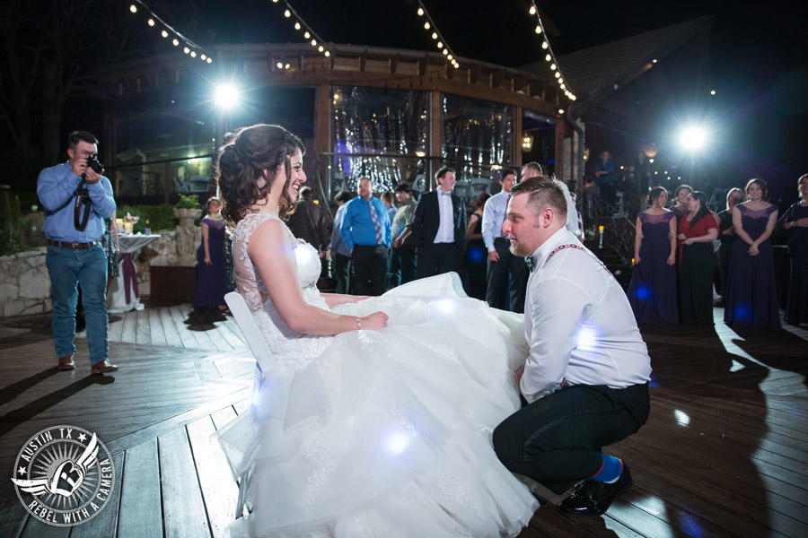 Lake Travis wedding pictures in Austin, Texas - Nature's Point - groom takes off the bride's garter during the wedding reception on the deck