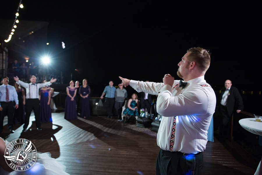 Lake Travis wedding pictures in Austin, Texas - Nature's Point - groom throws the garter during the wedding reception on the deck
