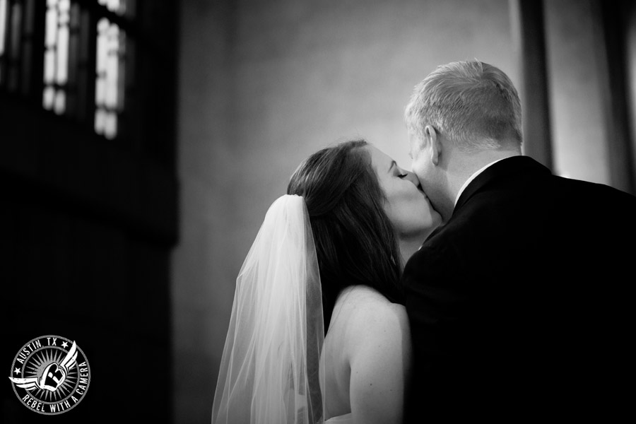 Wedding picture of bride kissing groom on the cheek during the wedding ceremony at St. Austin's.