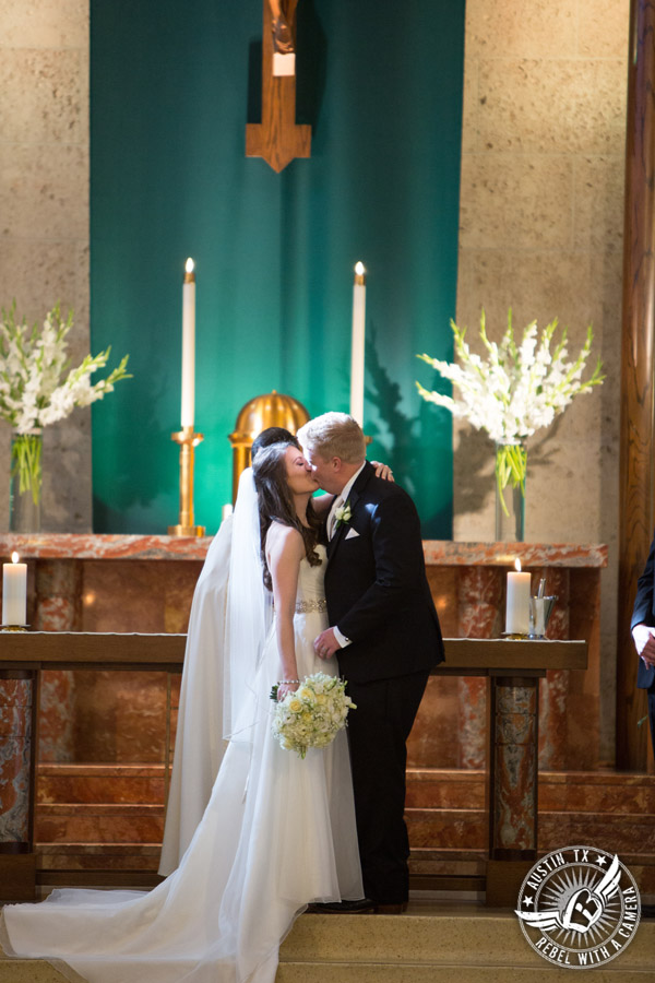 Picture of brtide and groom kissing during wedding ceremony at St. Austin's Church in downtown Austin, Texas