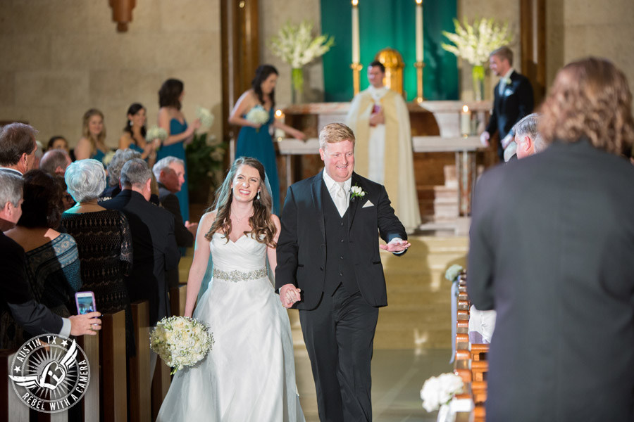 Picture of brtide and groom walking down the aisle at the end of the wedding ceremony at St. Austin's Church in downtown Austin, Texas