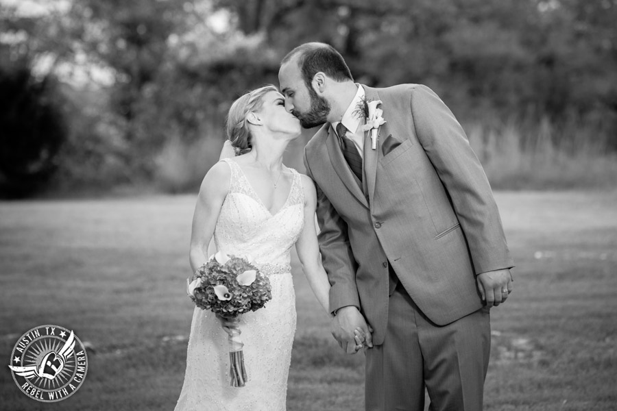 Fun wedding photographer at Kindred Oaks in Austin, Texas - bride and groom kiss in the meadow