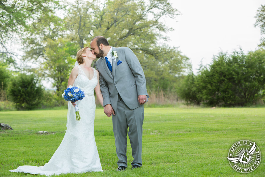 Fun wedding photographer at Kindred Oaks in Austin, Texas - bride and groom kiss in the meadow with blue hydrangea and white calla lily bouquet