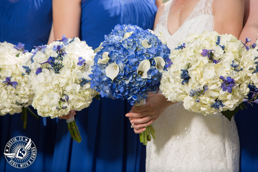 Fun wedding photographer at Kindred Oaks in Austin, Texas - bride and bridesmaids in royal blue dresses with blue and white hydrangea bouquets