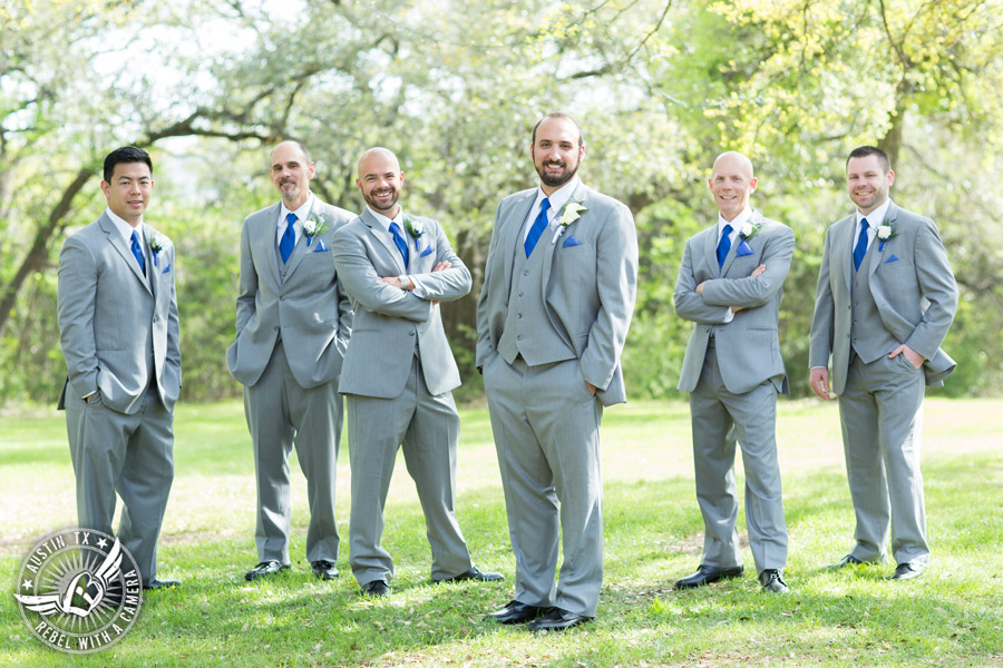 Fun wedding photographer at Kindred Oaks in Austin, Texas - groom and groomsmen in grey suits and royal blue ties
