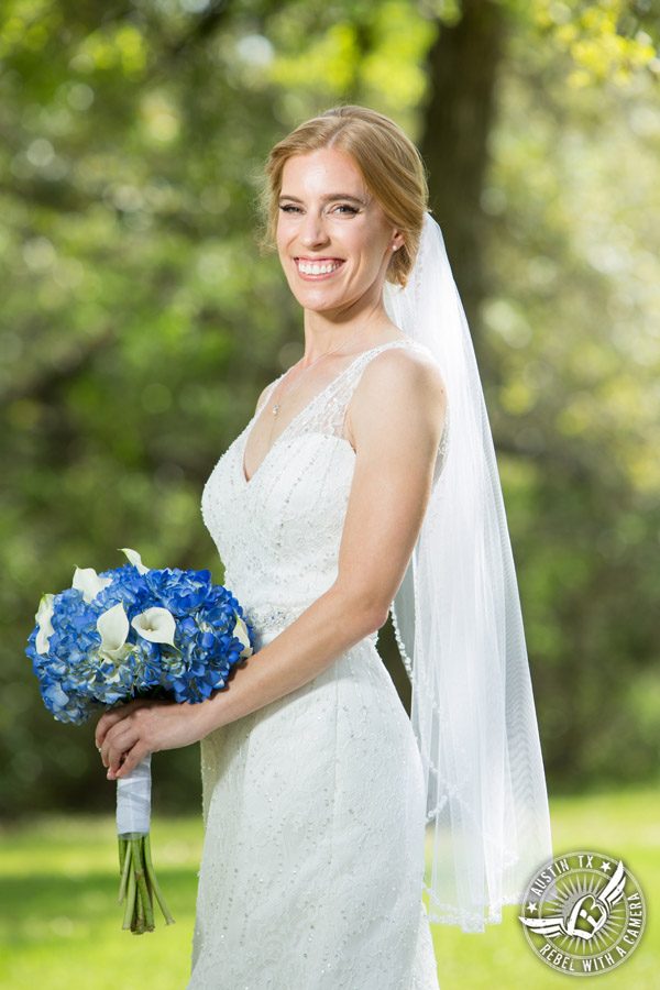 Fun wedding photographer at Kindred Oaks in Austin, Texas - bride in the meadow with blue hydrangea and white calla lily bouquet