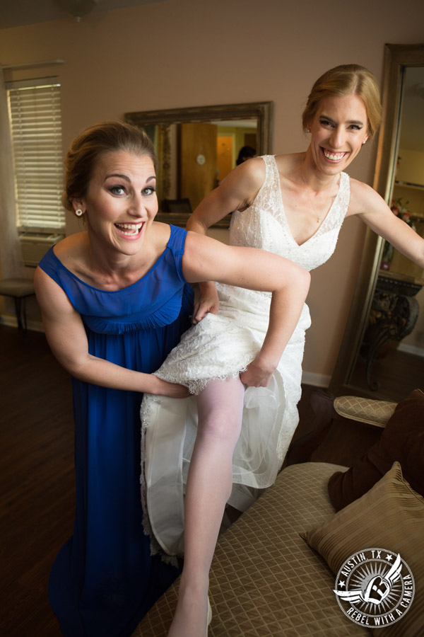 Fun wedding photographer at Kindred Oaks in Austin, Texas -bridesmaid puts garter on the bride in the bridal room
