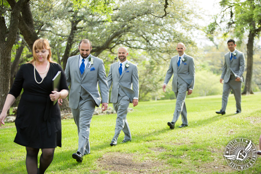 Fun wedding photographer at Kindred Oaks in Austin, Texas - groom and groomsmen walk to the ceremony with Sarah Reed wedding officiant of Let's Do it Vows