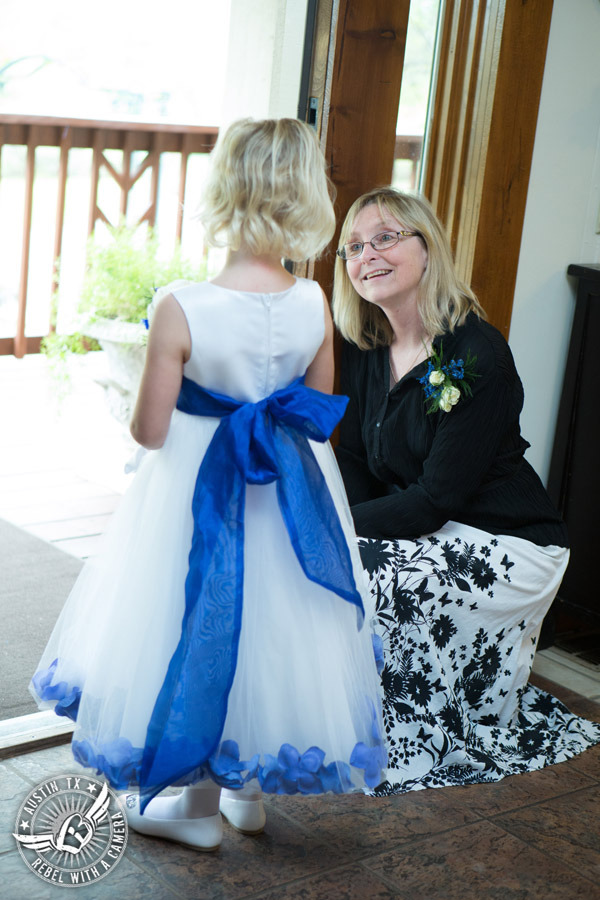 Fun wedding photographer at Kindred Oaks in Austin, Texas - Elaine Lincoln, owner of Kindred Oaks, helps flower girl get down the aisle