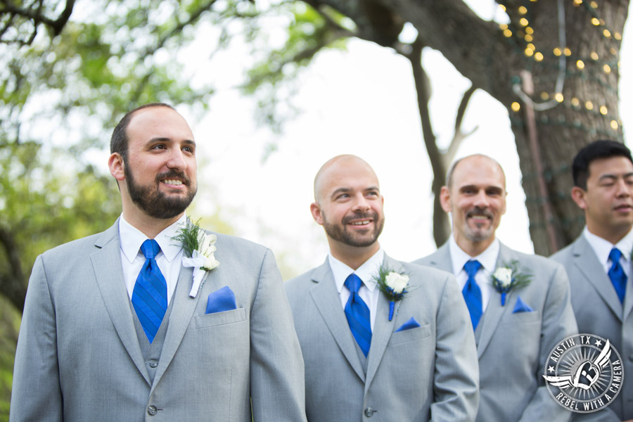 Fun wedding photographer at Kindred Oaks in Austin, Texas - groom sees the bride walk down the aisle escorted by her brother during the ceremony