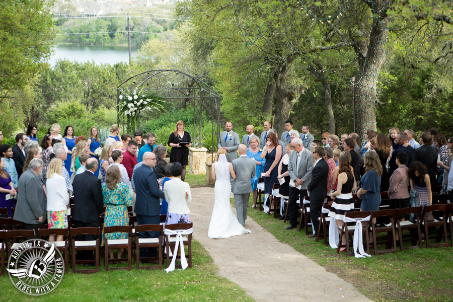 Fun wedding photographer at Kindred Oaks in Austin, Texas - groom sees the bride walk down the aisle escorted by her brother during the ceremony with Sarah Reed wedding officiant of Let's Do it Vows