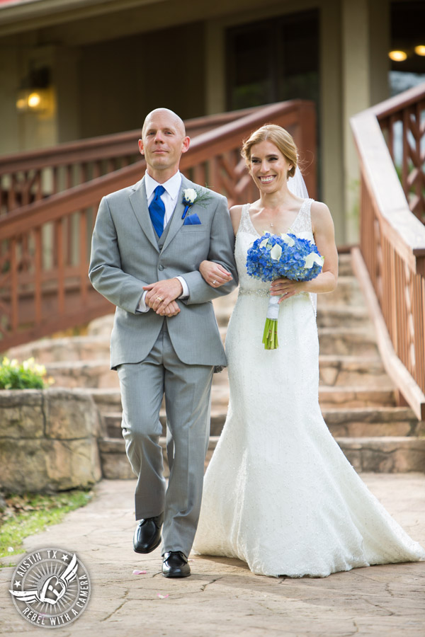 Fun wedding photographer at Kindred Oaks in Austin, Texas - bride walks down the aisle escorted by her brother to the ceremony