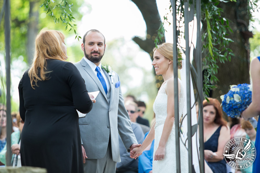 Fun wedding photographer at Kindred Oaks in Austin, Texas - bride and groom during the ceremony with Sarah Reed wedding officiant of Let's Do it Vows
