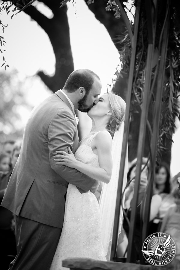 Fun wedding photographer at Kindred Oaks in Austin, Texas - bride and groom kiss at the end of the ceremony